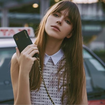 Model holding Bandolier iPhone case with strap