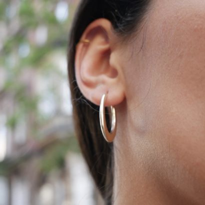 Model wearing 14K Solid Gold Weighed Oval Earrings Small Hoops