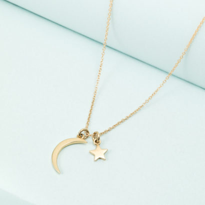Moon and star pendants on golden necklace