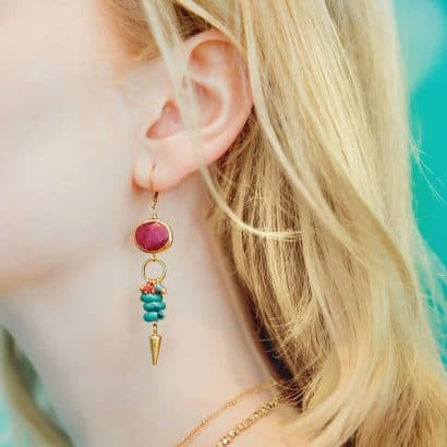 A white, blonde woman wears a gold earring (from top to bottom: gold encased oval-shaped ruby, gold vermeil circle, cluster of multi-colored stones, four flattened turquoise, and a gold vermeil spear).
