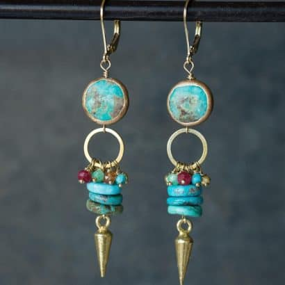 """A pair of bohemian earrings - from top to bottom: a gold-filled lever back hook, circular, smooth turqouise dipped in gold all around, and gold-dipped open circle, a cluster of mixed gemstones, tree flat circular turquoise pieces stacked on top of eachother, and a gold-dipped dart dropping about 2.5""""."""